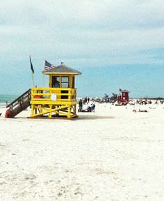 blue, yellow, red and green lifeguard stands line the siesta key public beach - they are staples