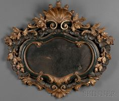French Painted and Gilded Mirror, 18th century, the cartouche-shaped mirror centered by dark green and gilt painted frame with shell-form finial topping decoration of scrolling foliage and flowers.