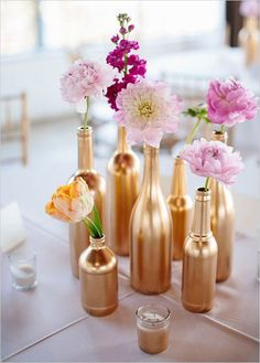 These recycled bottle bud vases are a great way to go green AND add an exciting punch of gold to your reception tables! See more pink and gold wedding ideas here. Photo by Sara & Rocky Photography