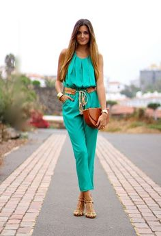 Teal jumpsuit w/ complicated belt, waistlength dark-rooted strawberry blonde hair, pink smile