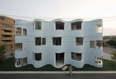 New Approaches to Apartment Living in Japan | Apartment in Higashi Fuchu   by Mejiro Studio.  The undulating facade of this apartment adds a sculptural character to the otherwise ordinary streetscape in Tokyo. Inside, the curved outer walls suggest separate rooms without doors and partitions.