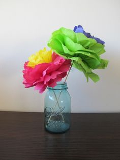 Are you sick of flower tutorials? This one uses napkins (but seems like it would work with tissue paper or crepe paper) and seems like it would be pretty easy to fold up and then fluff in San Diego.