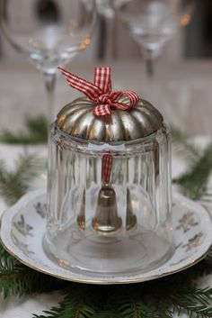 DIY Christmas bell from Sjarmerende jul. Drill a hole in the glass with a glass drill. Top the glass with a vintage metal mold. Drill a hole in this aswell. Hang a bell on a piece of ribbon.