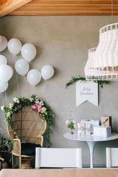 Boho mama-to-be seating area. Modern boho baby shower decor ideas. Balloons, florals, and garland.