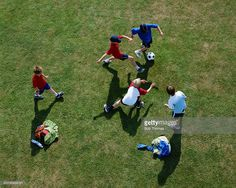 Stock Photo : Five boys (10-12) playing football, overhead view