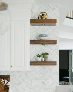 Here at The Tile Shop, we love a good shelfie! Rich wood shelves create a stunning contrast against the marble herringbone backsplash and white cabinetry.  ​Design by @almahomes. ​Photo by @oho_house. Decor, Herringbone Wall, Ceiling Decor, Wall And Floor Tiles, Marble Mosaic Tiles, Marble Mosaic, Wood Shelves, The Tile Shop, Small Decor