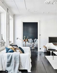 ornate white walls with pops of blue decor via sfgirlbybay | scandinavian boho vibes | dark wooden floors | relaxed white linen sofa cover | vintage plastic egg chair | get the look with a linen cover from Bemz for your IKEA sofa