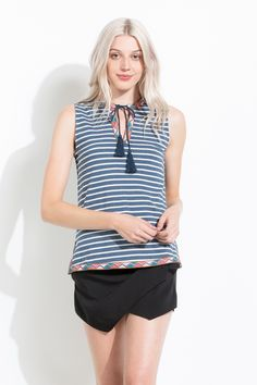 This striped top has a bohemian twist with the colorful triangle embroidery and the tassel detail.