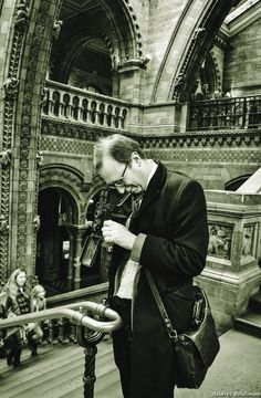 Man with a camera, inside the Natural History Museum in London
