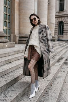 Fashion blogger Beatrice Gutu wearing chunky cable knit sweater with checked coat and fishnet tights at Berlin Fashion Week street style
