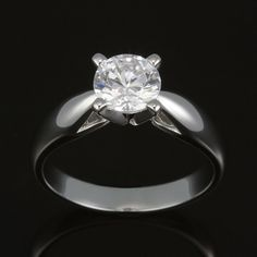Prong set diamond solitaire with inward tapered raised open arch shoulder band. Classic flowing open tapered lines enhance a prong set solitaire.  Try on this design in our showroom.