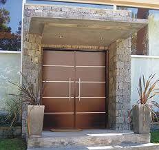 Puerta exterior, diseño vanguardista para esta combinación de puerta en madera con muros de piedra.