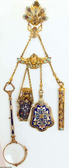 ENAMELED GOLD CHATELAINE, 1850-1890. Blue and red enamelled clasp over winged Pharaoh element, 4 chains holding magnifying glasses, perfume vial, note card and pencil.