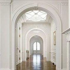 A series of arches punctuate this long gallery, leading visitors from the entryhall to the living room of our Penthouse Apartment project. Due to its location on the top floor of the building, we were able to include a new lay light above, allowing floods of sunlight to stream in and reflect off the matte white paneling and waxed, aged parquet de Versailles flooring. #AndrewSkurmanArchitects [Link to Full Project in Bio] 📷: @daviddlivingston