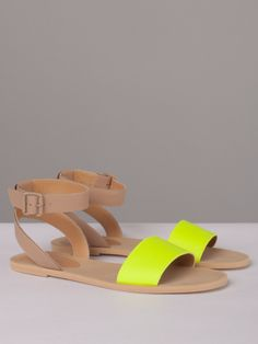 Flat sandals in beige leather with a posted ankle strap that buckles on outside, a wide neon yellow band at toe, and rubber micro soles. Made in Italy.