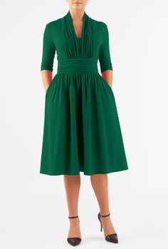 Our cotton jersey knit dress is styled with a pleated high back neck, deep V-neck front, wide banded waist with ruched pleating and a full skirt.