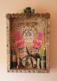 This is a found object assemblage of vintage sewing items. The shadow box is covered in vintage sewing patterns. The box is decorated with vintage wooden buttons, part of a vintage measuring tape, a vintage pin cushion and wooden spools of thread. Inside the shadowbox I have artfully displayed a small collection of vintage sewing items: small pieces of lace, an old crochet hook, needle threaders, vintage bobbins, vintage needles, vintage needle packets, wooden spools of thread, thimbles…
