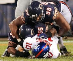 New York Giants quarterback Eli Manning (10) gets sacked by Chicago Bears linebacker Lance Briggs (55) and defensive end Corey Wootton