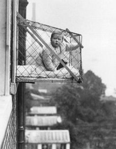 Popular Science Monthly circa 1923. Thanks to an English invention, babies are given fresh air in metal cages which are designed to attach to the outside window of a high-rise building with (only) the help of two iron poles.