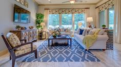 A fresh and inviting living room by Darling Homes at Creekside Park, Pondera Point with blue and yellow accents.