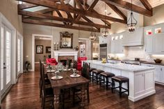 sherwin williams latte is one of the best neutral paint colours, shown in open layout kitchen and dining room with wood beams and white cabinets