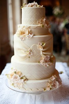 Exquisitely detailed classic multi tiered wedding cake with delicate vintage accents in a palette of ivory, cream and pink
