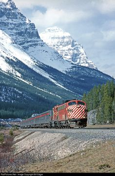 CP 1403 and a GP9 glide the eastbound Canadian over the top of Kicking Horse Pass under a backdrop of some of the most beautiful mountain peaks on the continent. This location is at or near the BC/Alberta border. Next stop Lake Louise.