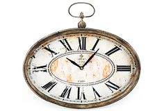This artful wall clock boasts a unique oval shape and antique-inspired finishings