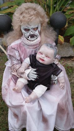 Creepy Halloween yard display using large dolls to create a zombie grandmother and grand baby duo.