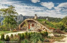 an amazing example of a hobbit-style earth sheltered home with grass roof