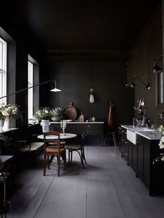 Un univers riche, élégant, feutré , parquet gris fumé , mur noir ébène , cuisine rétro noire, chaise et banc Thonet.
