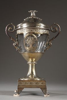 A silver and crystal sweetmeat basket decorated on the rim with two medallions with flowery baskets delicately chiselled and a frieze of interlace with flowers. Heads of greyhounds decorate