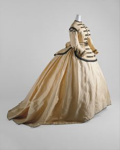 Military-style decoration was recapitulated in civilian clothing, as seen in the front closure, shoulders, and cuffs of the bodice of this dress, although the actual decoration is here deliberately feminized