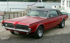 """1967 Mercury Cougar.  In dark red this time.  The introduction of the Cougar finally gave Mercury its own """"pony car"""".  The Cougar was the performance icon and eventually the icon for the Mercury name for several decades.  The Cougar was available in two models (base and XR-7) and only came in one body style (a two-door hardtop, no center or B-pillar).  A performance package called the GT was available on both the base and XR-7 Cougars."""