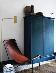 Navy-painted, matte-finished wardrobe looks sleek with modern leather chair.
