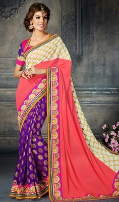 Designer purple, off white and tomato embroidered georgette jacquard sari is perfect for evening party requirement. Sari is ornamented with self woven motifs, lace, silk thread embroidered border and crystal stones which makes you too look quite stylish and graceful. Sari pairs with contrast purple, pink raw silk stitched blouse as shown in the picture. #NewPatternTraditionalSarees