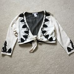 White House Black Market cropped sweater Cream with black appliqué, ties in the front, cropped. Lined and 70%silk. Very sweet!! White House Black Market Tops