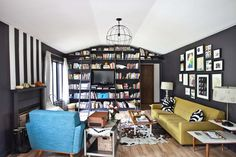 I like the combination of black wall & white ceiling, black book case & black picture frames here,