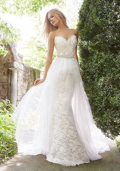 Ivory / cashmere Alencon Lace trumpet bridal gown with sparkle throughout. Strapless sweetheart neckline with a sheer corset back. Shown with a detachable tulle overskirt and jeweled belt at the natural waist.