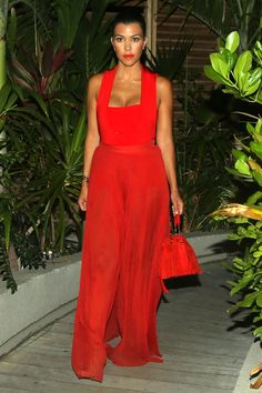 Kourtney Kardashian steps out in a red statement-making jumpsuit while in St. Barths. Shop her look here: