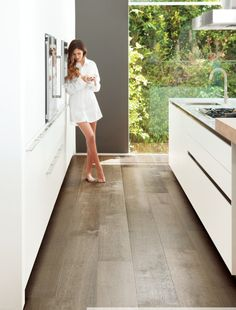 Example of Extra wide plank wood floor by porcelanosa with white kitchen. also white slab cabinets with hardware
