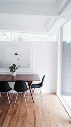 White walls, white planked ceiling, walnut table, black shell chairs and neutral…