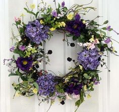 This handcrafted front door wreath is so colorful and beautiful that you can display it all year long. This magnificent wreath is 23 inches in diameter and is a spectacular piece for your front door, but equally beautiful indoors on a wall, over your mantle or even on an inside door. Our wreaths are custom made to ord