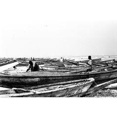 """Opera dell'archivio dell'agenzia """"D.F.P"""", fondata da Dani Maria Turriccia nel 1963. La fotografia appartiene a un reportage, condotto in Nigeria nel 1975. I pescatori sono rientrati da una battuta di caccia, il mare sullo sfondo è agitato. Il taglio obliquo dell'imbarcazione in primo piano conferisce maggior profondità, lo sguardo scorre verso il cielo, oltre la linea dell'orizzonte. Africa, Nigeria 1975."""