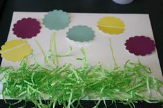 Spring Flowers: An Easy Craft.  I like how they use leftover Easter grass for the grass in the picture!