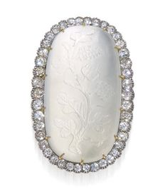 An antique moonstone and diamond brooch, circa 1900  centering an oval cabochon frosted moonstone carved in a foliate motif, within a surround of old mine-cut diamonds; estimated total diamond weight: 3.00 carats; mounted in platinum topped eighteen karat gold; length: 1 1/2in.