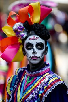 """A girl dressed as a """"Katrina"""" waits for the start of a Day of the Dead parade to begin along Mexico City's main Reforma Avenue, Saturday"""