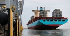 Close to land: The huge ship - which weighs 115,000 tonnes when fully loaded - is towed into port