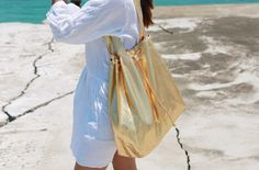 【iamyuri】ポリエステル混紡素材を使った巾着バッグです。 キラキラメタリックなカラーがインパクトのあるアイテム☆ 大きめサイズで収納力が抜群です♪ カジュアルなビーチルックにオススメ!!