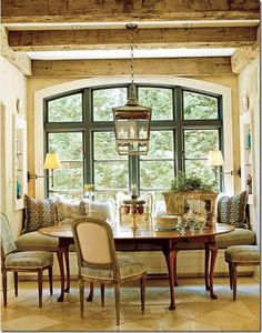 casual elegance, oval table with plush window banquette, rustic beams, twin display niches